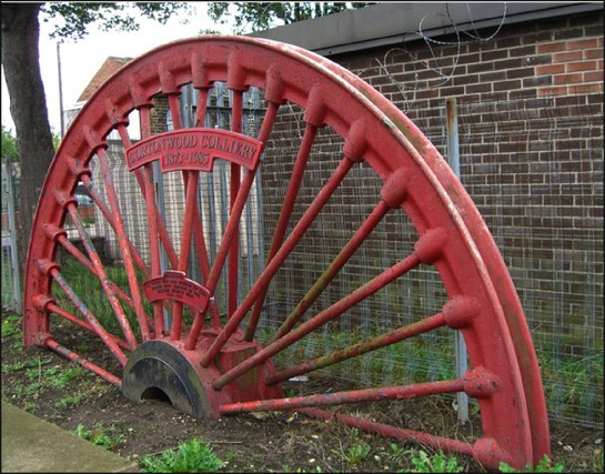 Figure 1:  Pit winding wheels are often set as memorials to both killed workers and former collieries in these communities.  This example, from Cortonwood Colliery, is adjacent to Brampton's war memorial.