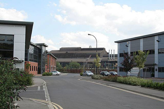 Text Box: Figure 1: 'New and Old in Brightside' – In the foreground are office buildings of 'Jessop's Riverside' an early 21st Century commercial development of a former steelworks site.  In this zone such developments typically sit alongside surviving industrial complexes.  In the background are the Electric Arc Melting sheds of Sheffield Forgemasters